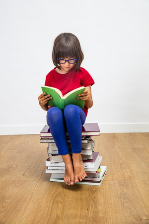 beautiful young elementary schoolgirl with eyeglasses reading, seated on top of a stack of books for female studying and culture power on white background, indoor