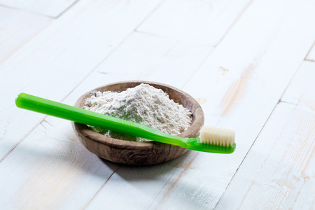 neutralizer: Healthy natural dental care and hygiene with green toothbrush and ecological baking soda salt in wooden cup, still life top view