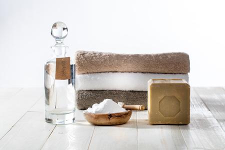 Lavandería de limpieza sostenible con detergentes y suavizantes caseros elegantes con jabón tradicional de Marsella, vinagre y bicarbonato de sodio para toallas dobladas mullidas sobre fondo de madera
