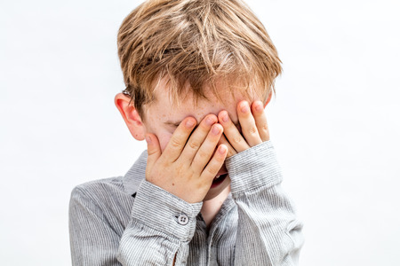 cute little boy covering his face for playing peekaboo, hide and seek, disappearing or being shy over white background, indoors 版權商用圖片