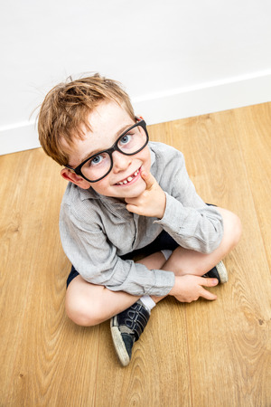 gifted: smiling adorable boy with smart eyeglasses and tooth missing seated on the floor thinking, looking up for concept of gifted education and reflection, high angle view Stock Photo