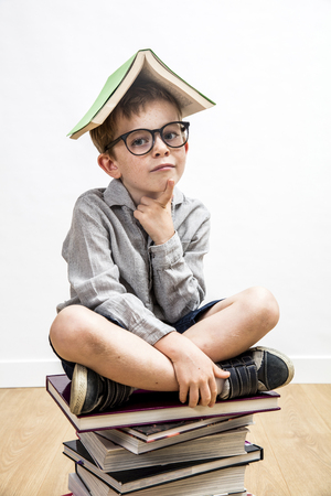 portrait of thinking little child with smart eyeglasses with a book on his head having education and school thoughts seated on top of a pile of books on white background and wooden floor