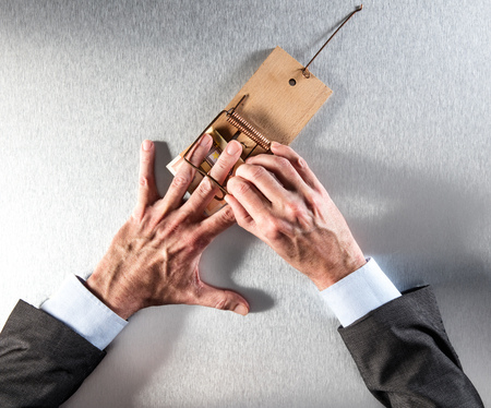 businessman removing his hand a mouse trap with a bank note for concept of corporate greed, danger, warning or money question, above view