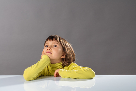 smiling imaginative little child looking away, thinking and daydreaming for concept of kid curiosity, freedom, intelligence, future and open-mindness to protect, copy space
