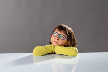critical thinking: kids critical thinking with serious little child leaning her head on a school table, looking away with imagination, reflection, doubt and gifted thoughts about future, copy space