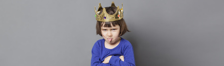 spoiled kid concept - cheeky preschool child with golden crown on head folding arms and sticking out tongue for disrespectful mollycoddled little king or queen metaphor, long grey banner