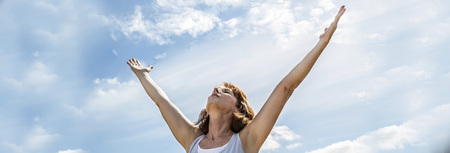 breathing outside - zen middle aged yoga woman looking up and raising her arms up, practicing meditation for freedom over summer blue skies, low angle view, long banner Stock Photo
