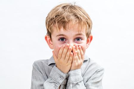 schöner freudiger 6-jähriger Junge mit den großen blauen Augen, die sich vom Bersten mit dem Lachen mit den Händen zurückhalten, die seinen Mund für Schüchternheit oder Glück über weißem Hintergrund bedecken