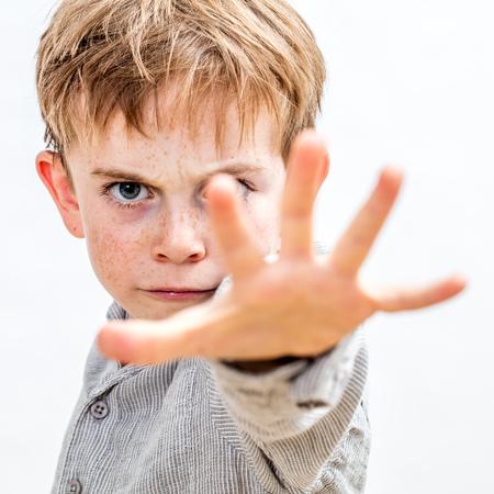 erschrockenes 6-jähriges kleines Kind mit der Hand vorwärts verteidigend sich, stoppend Gewalt oder Missbrauch in der Schule, oder benehmend wie ein Tyrann oder ein Gör drohender Vorschüler, weißer Hintergrund