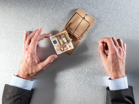 tempted businessman hands taking a euro bank note from a mouse trap for corporate theft, bait or investment question, top view
