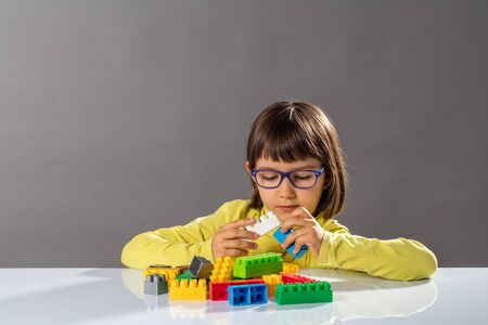 concentrated young child with eyeglasses playing with building blocks on desk, thinking about her future engineer career or organizing her imagination, copy space