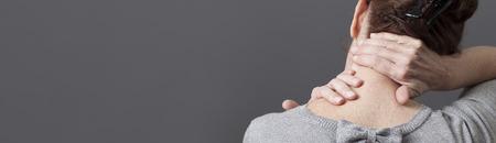 gesti del collo e delle spalle per rilasciare la tensione nella schiena per la donna di mezza età, panorama lungo grigio Archivio Fotografico