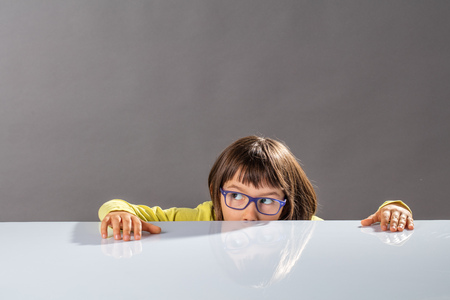 fun kid with eyeglasses hiding half of face below a desk, looking away for an idea to escape, playing serious hide and seek using her playful imagination, grey background