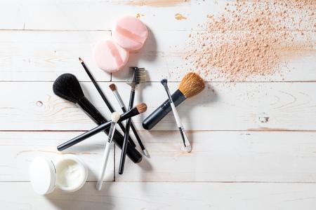 Konzept von Kosmetik und von Make-up mit freiem Pulver, Hautpflege und verschiedenem Fachmann bilden Gesichtsbürsten über weißem hölzernem Hintergrund für eleganten Schönheitshintergrund, Ebenenlageansicht