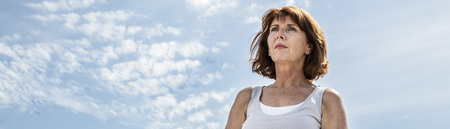 breathing outdoors - beautiful middle aged woman sitting on a stone in yoga lotus position, wearing white, seeking for balance over summer blue sky,low angle view, long banner Banque d'images