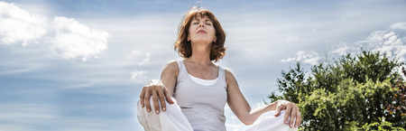Exercising outside - radiant 50s yoga woman sitting on a stone, seeking for spiritual balance with tree, low angle view, a long banner