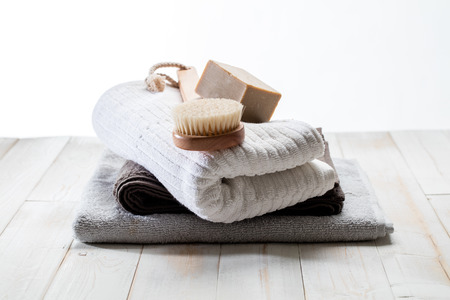 body brush, solid soap and pile of cotton towels for green friendly shower or traditional bath concept over white wood background, still life in studio Stock Photo