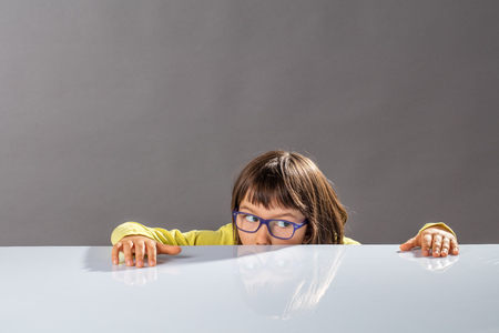 concept of education with concerned little child with eyeglasses hiding half of his face below a table, looking on the side for an idea to escape, playing peekaboo using fun imagination, grey background