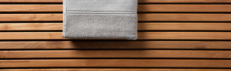 Half grey towel for spa, hammam, sauna, shower, bath, hygiene or body care concept with grey cotton towel set over beautiful wooden board, copy space long banner Banque d'images