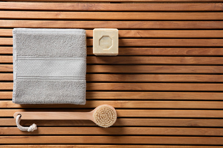 Still life for eco-friendly shower, hygiene, bath, sustainable spa or traditional body care concept with body brush, solid soap and towel over beautiful wooden board, copy space wallpaper, top view Banque d'images