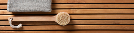 Still life for shower, freshness, hygiene, bath, dry brushing, spa or body care concept with body brush and half grey towel over beautiful wooden board, beauty spa copy space panorama, top view