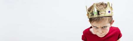 long banner of rebellious beautiful spoiled kid with frowning freckles wearing a king crown for mad attitude facing parenthood and education, white background, high angle view