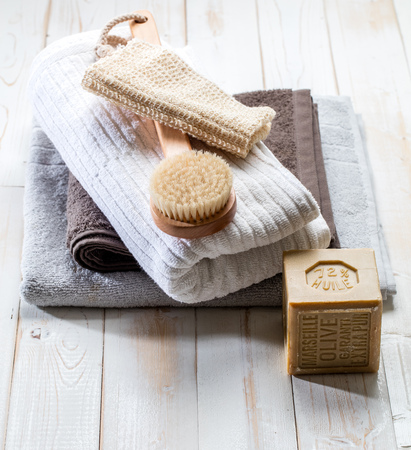 clean beauty and design still life for body and environment respect with exfoliating loofah, solid extra pure Marseilles olive oil soap, brush and beautiful cotton towel