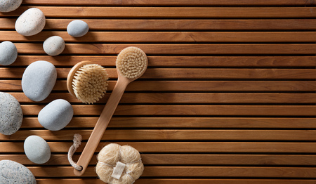 zen pebbles set on Turkish bath wooden board with exfoliating body brushes for eco-friendly spa, massage or sauna, copy space still life, top view