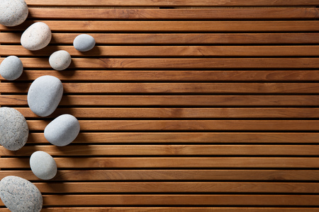 zen stones set on design wooden board for concept of spa, massage, mindfulness or wellbeing, copy space still life, top view Stock Photo