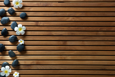 black massage pebbles and spa flowers set on design wooden board for zen spa, hammam, sauna or pure shower, copy space still life, above view Stock Photo