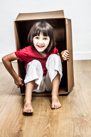 excited 6 year old girl sitting in a cardboard box playing for happy surprise, fun moving day or hiding in new home for imagination, one real person Stock Photo