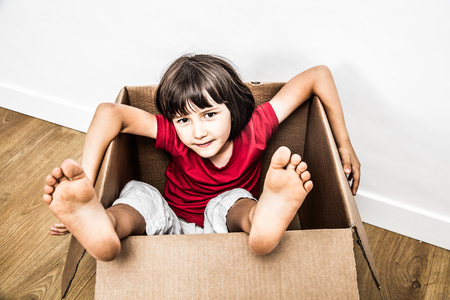 relaxed 6 years old child sitting in an old cardboard box with feet out playing for fun, building toy, moving day or hiding in new house, one real person