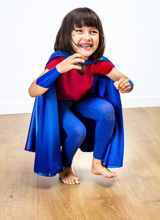 beautiful giggling super hero child with a blue cape playing, jumping for exciting childhood and joyous freedom and female power over wooden background Banque d'images
