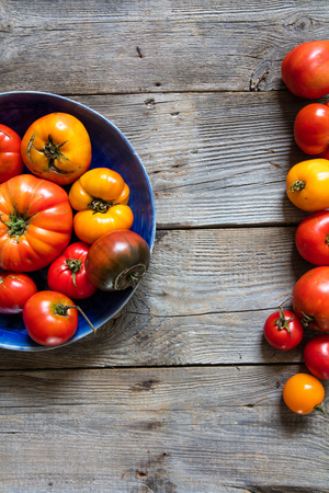 colorful halved plate and border of rustic red and yellow tomatoes for organic vegetarian menu over natural old wooden table for vertical top view banner, vitamins still life