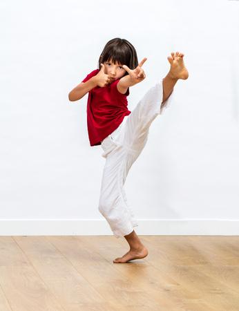 gericht jong kind dat dynamische gratie en positieve energie toont met vechtende benen en vingers voor de krijgskunst en motivatie van kinderen over houten vloer, witte achtergrond