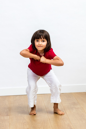 Cheerful energetic young child enjoying expressing herself with dynamic body language and joyful motivation over wooden floor, white background