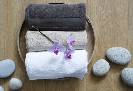 Closeup of pampering towels and zen stones on round wooden background for concept of pure sensuality, clean softness or female bodycare, top view still life