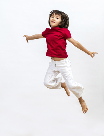 A happy young girl jumping and flying high to express freedom, open mindedness, imagination, happiness and joy over white background