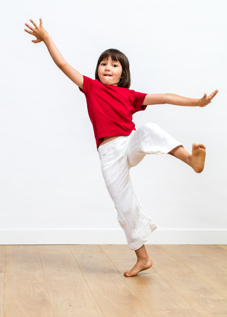 excited young child fainting to fall in practicing martial arts or gym, playing unbalance with bare feet and raised arms over wooden floor, white background