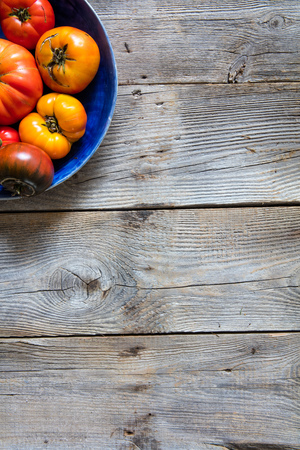 Earthy halved plate of colored cracked heirloom tomatoes for organic vegetarian menu over sustainable old wooden background for vertical top view copy space banner