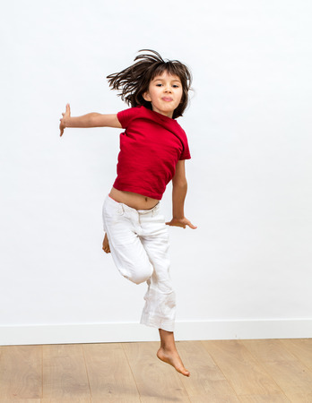 happy beautiful young girl jumping with positive energy, flying high to express joyful success, dynamic childhood and fun sports over wooden floor, white background