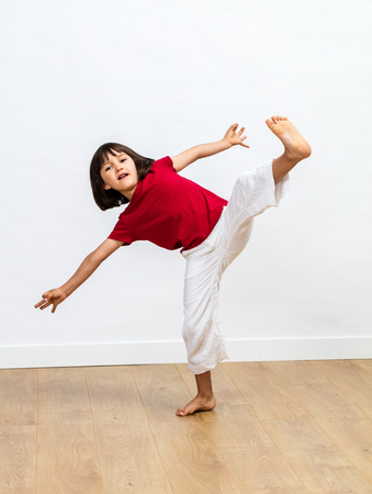 dynamic young child with bare feet enjoying fighting with exercice of tai chi, kung fu or taekwondo, playing in falling for fun kids martial arts over wooden floor, white background