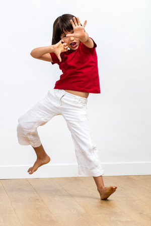 excited sporty young child with dynamic gesture fighting, showing energetic grace and power with dancing legs and hands for kids martial art over wooden floor, white background Фото со стока