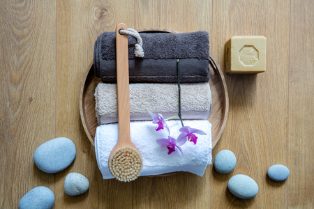 dry brushing, pampering towels, orchids and eco-friendly soap over zen stones on round wooden background for chic wellbeing, shower, bath or fresh massage, above view still life Фото со стока