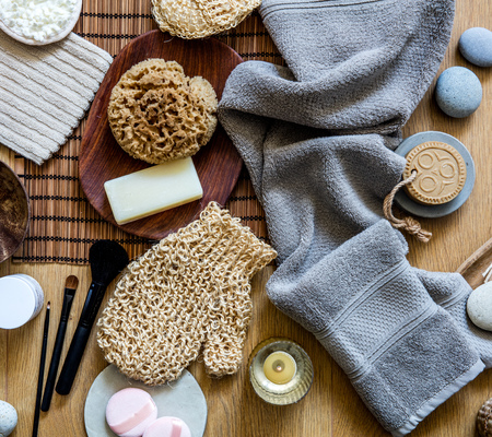beauty mix of traditional and zen body care objects for genuine shower or bath with natural sponge, loofah, towel, solid soap and makeup brushes, top view Фото со стока