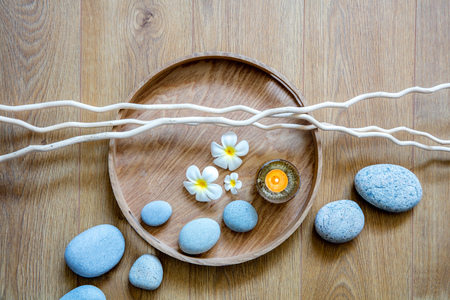 spa decor for chic ayurveda, natural beauty, mindfulness or zen massage with a flow of stones, a candle, flowers and twigs over round wooden tray, top view still-life
