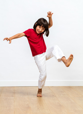 joyful little child playing monster or tiger with kids tai chi or kung fu sporty gestures, showing kids fighting body language over wooden floor, white background