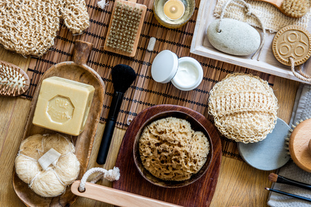 body care concept of traditional and zen objects for healthy shower or bath with zero waste loofah, natural sponge, olive oil soap, face cream, manicure and makeup brushes, top view