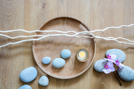feng shui decor for chic ayurveda, female beauty, mindfulness or zen massage with a flow of stones, a candle,orchids and twigs over round wooden tray, above view Imagens