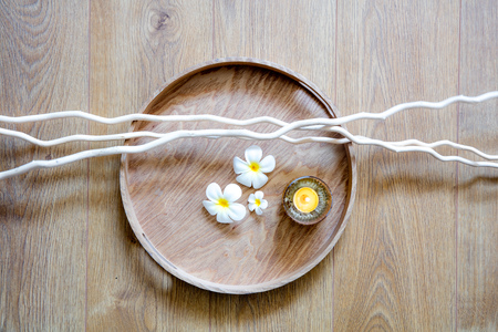 still-life of detox round wooden tray, candle, zen twigs and beautiful flowers for mindfulness, feng shui, meditation or sensual massage, top view